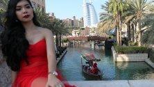 """Жена позира за снимка докато мъже, облечени като Дядо Коледа, минават с лодка с туристи към селото на Дядо Коледа, а отзад се вижда луксозния небостъргач """"Бурж ал Араб"""", Дубай, ОАЕ."""