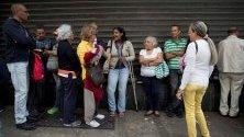 Хора чакат на опашка пред магазин, който приема петро като разплащателна единица, в Каракас, Венецуела. Парите бяха раздадени от президента Николас Мадуро като коледен бонус.
