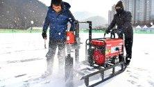 Работници пробиват дупки в леда за лов на пъстърва в Южна Кореа
