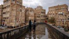 Йеменки минават край исторически сгради след проливни дъждове в стария квартал на Сана.