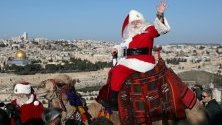 Група мъже и жени от целия свят, преоблечени като дядоколедовци, посещават Хълма на маслините над Ерусалим.