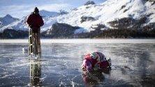 """Хора се пързалят по езерото Зилзерзее, покрито с т.нар. """"черен лед"""", в Зилз, Швейцария. Черният лед е много опасен, тъй като е само лек замръзнал пласт на повърхността."""