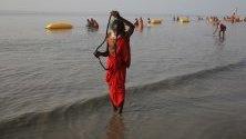 Монах взима баня на брега на Бенгалския залив по време на Ganga Sagar Mela на Остров Сагар, Индия. Ganga Sagar Mela е годишно събиране на вярващи индуси, които извършват ритуални къпания за прочистване на душите в река Ганг.