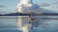 Рибари ловят с мрежи край изригващия вулкан Таал във Филипините.