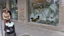 Ливанци минават край разрушена витрина на Банката на Бейрут след антиправителствени протести в града.