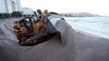 Булдозер размества купчини пясък на плажа Риасор в Ла Коруна, Галисия, Испания. Пясъкът беше раздухан от силните ветрове по време на редицата бури, които преминаха през Испания през последните седмици.