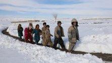 Деца вървят през снежните преспи в провинция Балочистан, Пакистан. Близо 90 души загинаха заради снеговалежи и лавини в региона.