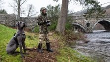 Рибар и неговият дог ловят риба в река Тей в Шотландия по време на откриването на сезона за улов на пъстърва.