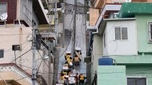 Доброволци от Червения кръст на Южна Корея се катерят по стълби в град Бусан, за да доставят помощи на уязвими хора.