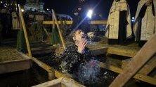 Свещеник наблюдава пречистване в студени води по време на Богоявление в Москва, Русия.