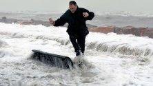 Вълни заливат човек на променадата в крайбрежното градче Алменара, Испания. Бурята Глория бушува по източното крайбрежие, взимайки най-малко три жертви.