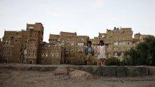 Деца са застанали пред исторически сгради в стария квартал на Сана, Йемен, обхванат от военен конфликт от 2014 г.