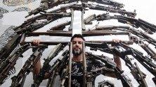 Мексиканският творец Алваро Куевас позира със скулптурата си, направена от оръжия, в Гуадалахара, Мексико. Куевас трансформира 12 тона оръжия в скулттури.