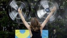 Тенис фен се охлажда на вентилатор с вода по време на Australian Open в Мелбърн, Австралия.