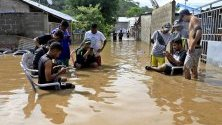 Хора сред наводнена улица в Дили, Източен Тимор. Проливните дъждове потопиха под вода части от столицата.