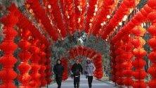 Хора се разхождат през тунел от червени фенери в Пекин преди настъпването на Китайската нова година на 25 януари.