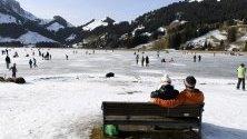 Хора се радват на слънчевото време, карайки кънки върху замръзналото езеро Шварцзее на 1045 м. над морското равнище в Източен Фрибург, Швейцария.