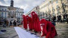Протестиращи в червени костюми в Лисабон, Португалия, правят лодки от хартия в памет на загиналите мигранти при опит да достигнат Европа по море.