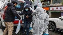 Медицински работници в защитни костюми помагат на пациент да слезе от линейка в болница в Ухан, Китай. Коронавирусът досега е погубил най-малко 80 души, а около 2000.