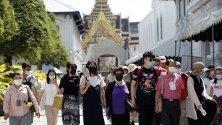 Туристи с маски из Големия дворец в Банкок, Тайланд, в опит да се предпазят от коронавируса.