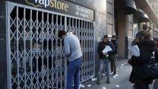 Търговец затваря магазина си докато синдикалисти го окуражават да се присъедини към общата стачка в Билбао, Испания.