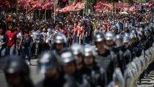 Полицаи маршируват редом до протестиращи в Буенос Айрес, Аржентина, настояващи за мерки срещу бедността.