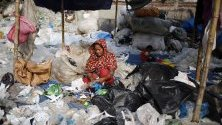 Работник преглежда пластмасови боклуци за рециклиране край река Буригангав Дака, Бангладеш. Страната е една от най-замърсените в света.