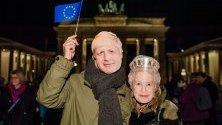 Проевропейски привърженици с маски на британския премиер Борис Джонсън и британската кралица Елизабет Втора минути след полунощ, след като Великобритания напусна Европейския съюз, демонстрират пред Бранденбургската врата в Берлин.