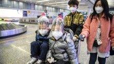 Деца носят защитни маски и импровизирана защита върху лицата си от пластмасови бутилки срещу коронавируса на летището в Гуанджоу, Китай.