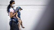 Жена и бебе със защитни маски срещу коронавируса по улиците на Банкок, Тайланд.