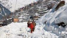 Местни жители вървят из преспи, паднали след лавина, Кашмир, Пакистан. Най-малко 90 души са загинали при различни инциденти с лавини в региона през последните дни.