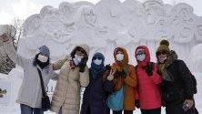 Посетители на снежния фестивал в Сапоро, Япония, позират със защитни маски срещу коронавируса.