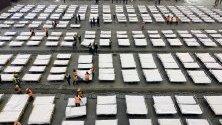 Работници подреждат легла в мобилна болница с 2000 легла в Ухан.
