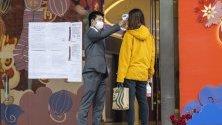 Охрана на търговски център проверява влизащ клиент в Гуанджоу, Китай.
