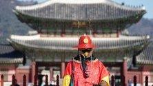 Южнокорейски гард в традиционни дрехи и защитна маска срещу коронавируса на стража пред двореца в Сеул.