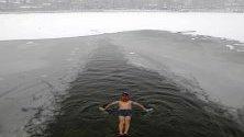 Ентусиаст плува в ледените води на полузамръзналото езеро Хухай в Пекин, Китай.