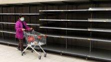 Пазаруващ минава край празни стелажи в Хонконг. Хората там все повече се презапасяват със стоки от първа необходимост.