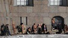 """Руснаци си взимат слънчеви бани край крепостта """"Петър и Павел"""" в центъра на Санкт Петербург, Русия. Температурите паднаха до около -6 градуса."""