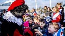 Преоблечен като Черния Пит поздравява деца в село Гру, Холандия. Според легендата Синт Питер е брат на Sinterklaas и идва два месеца след него. Той е винаги придружаван от Черния Пит.