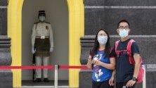 Туристи със защитни маски срещу коронавируса минават край двореца в Куала Лумпур, Малайзия.