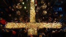 """Огнен кръст пламна символично в благоевградския храм """"Въведение Богородично"""". По традиция в Деня на пчеларя медът се освещава, като бурканчетата на стопаните се подреждат във формата на кръст, а привързаните за тях свещи се запалват."""