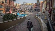 Жена със защитна маска срещу коронавируса минава из празен търговски център в Пекин, Китай.