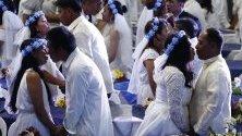 Двойки се целуват по време на масова сватба в Деня на влюбените в Манила, Филипините.