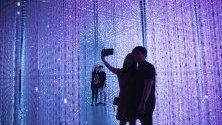 """Посетители се снимат с интерактивна дигитална инсталация част от изложбата """"Бъдещ свят - изкуството се среща с науката"""" в ArtScience музея в Сингапур."""