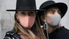 Посетители на Седмицата на модата в Лондон носят модни маски за лице срещу коронавируса.