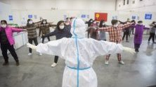 Пациенти, поставени под карантира заради коронавируса, правят физически упражнения с медицински служител във временна болница в Ухан, Китай.
