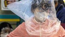 Жена от Гуанджоу, Китай, носи защитна маска срещу коронавируса и се е защитила допълнително с найлонова торба върху себе си.