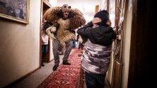 Преоблечен мъж в традиционен костюм плаши гостите в хотел преди да премине по улиците на село Арола, Швейцария, част от карнавала Еволене.