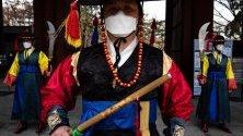 Южнокорейски гвардейци със защитни маски срещу коронавируса изпълняват церемониалните си функции пред двореца в Сеул.