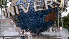 Туристи със защитни маски срещу коронавируса позират за снимка пред глобуса на Universal в Resorts World Sentosa в Сингапур.